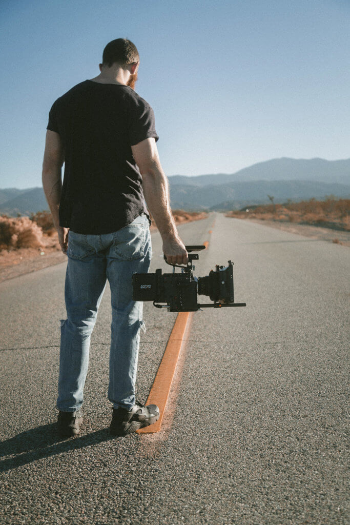 man standing in highway with camera